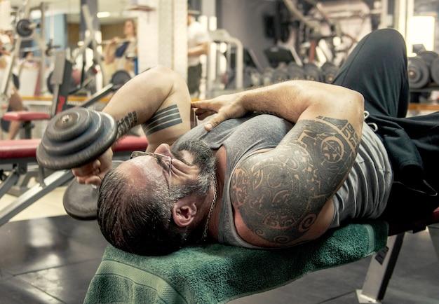 Bodybuilder soulever le poids avec le tatouage sur les biceps musculaires