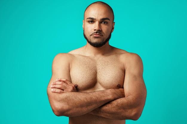 Bodybuilder avec torse nu debout contre turquoise