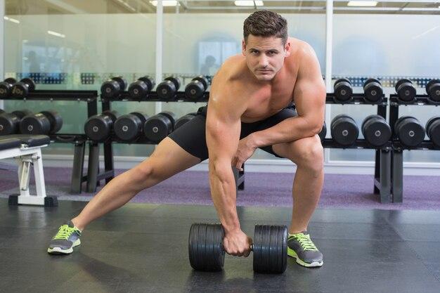 Bodybuilder torse nu soulevant lourd haltère noir dans une fente