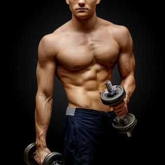 Bodybuilder torse nu tenant haltère et montrant ses bras musclés.