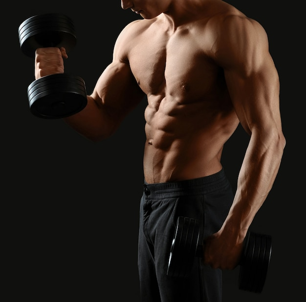 Bodybuilder torse nu travaillant avec des haltères montrant son torse tonique