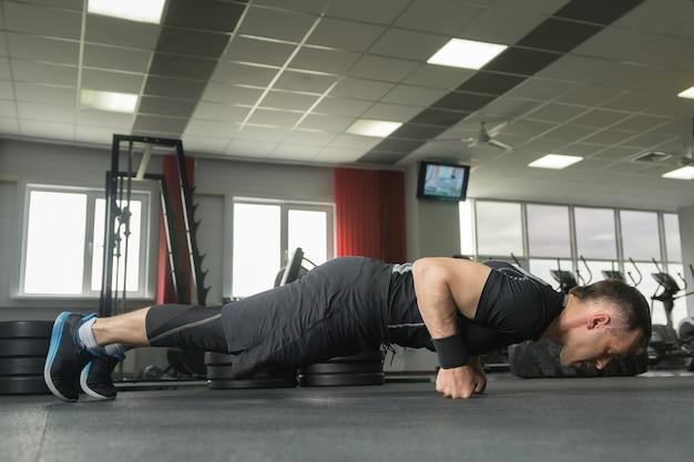 Bodybuilder travaillant et faisant des pompes sur les poings au gymnase.