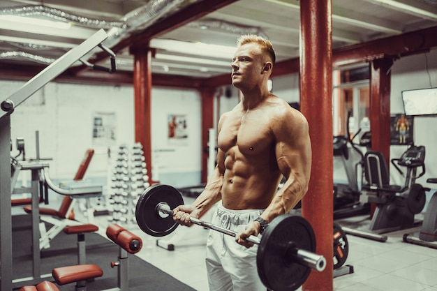 Bodybuilder de type athlétique très puissant, faites de l'exercice avec des haltères