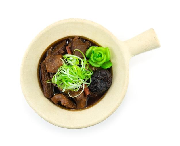 Boeuf braisé chinois et champignons dans un pot d'argile sur une escalope d'oignon de printemps vue de dessus
