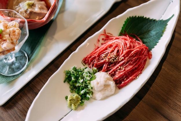 Le bœuf cru wagyu tranché en ligne, comme une nouille, servi avec un oignon vert émincé et du daikon.