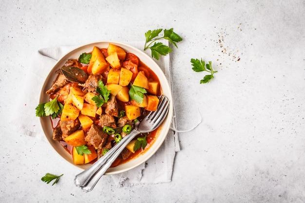 Bœuf cuit aux pommes de terre à la sauce tomate. viande goulache traditionnelle, copie espace.