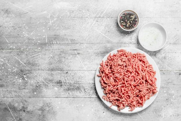 Bœuf haché cru aux épices. sur un fond rustique.