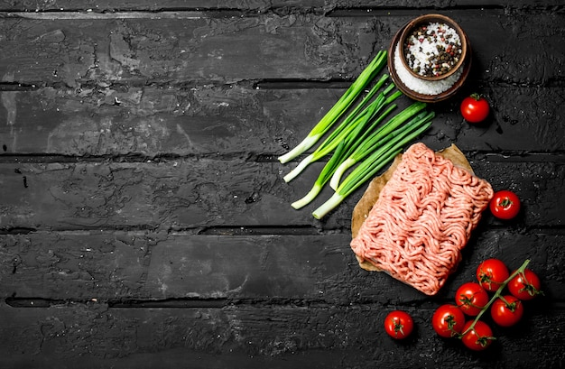 Bœuf haché cru aux tomates et oignons verts. sur fond rustique noir.