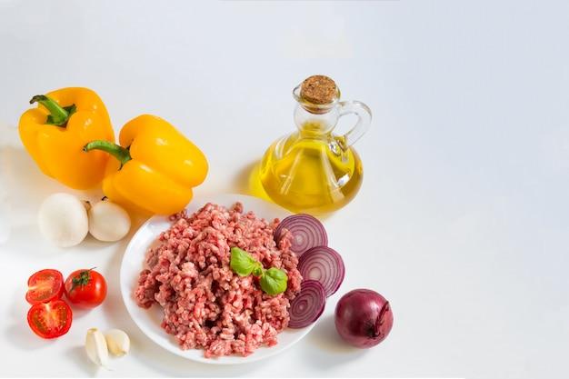 Bœuf haché cru frais dans une assiette blanche avec poivrons, oignons et tomates
