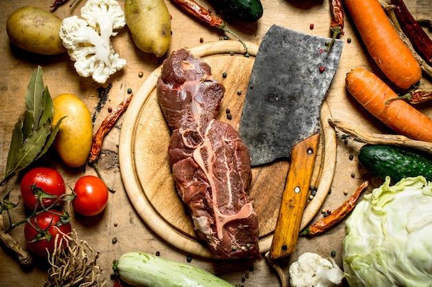 Boeuf avec une hache de viande et ingrédients pour la soupe
