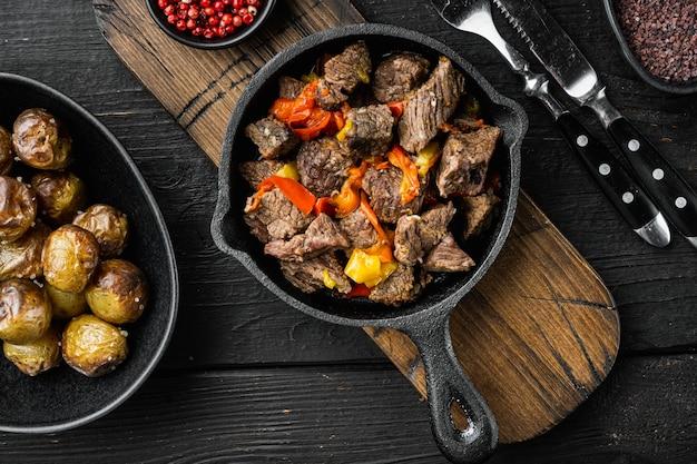 Bœuf mongol, morceaux de bœuf cuit dans de la sauce soja, dans une poêle en fonte, sur bois noir