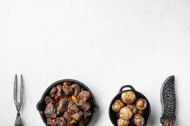 Bœuf mongol, morceaux de bœuf cuit dans de la sauce soja, dans une poêle en fonte, sur une surface en pierre blanche, vue de dessus à plat