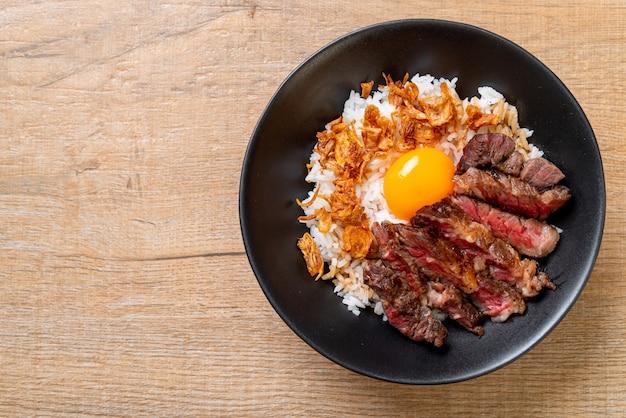 Boeuf tranché sur un bol de riz avec oeuf