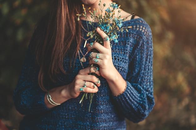 Boho chic femme en pull bleu tricoté et portant des bagues en argent avec pierre turquoise avec bouquet de fleurs sauvages dans les mains dans la forêt d'automne à l'extérieur à l'automne