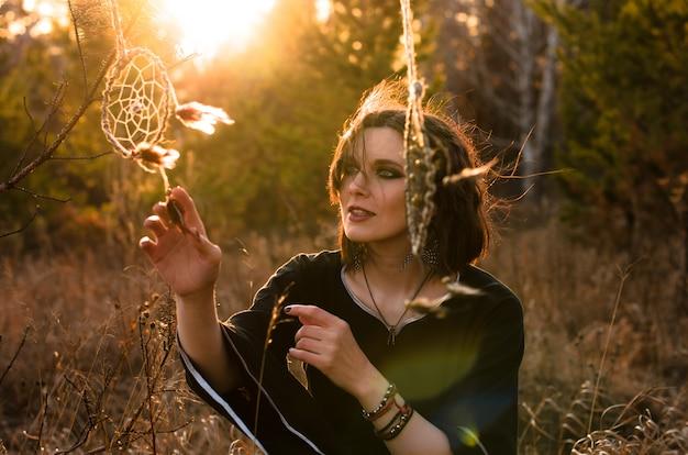 Boho femme aux cheveux courts et venteux. silhouette féminine avec capteur de rêves à travers les rayons du soleil