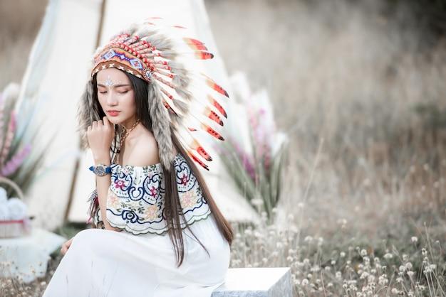 Boho fille de style bohème portant une robe maxi indienne et des bijoux en automne champ