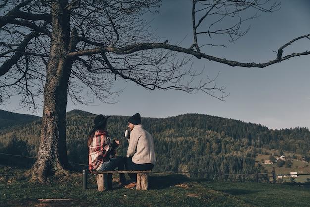 Boire des boissons chaudes. vue arrière du jeune couple buvant un tee chaud alors qu'il était assis sur le banc dans les montagnes