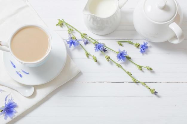 Boire de la chicorée dans une tasse sur la table en bois blanc