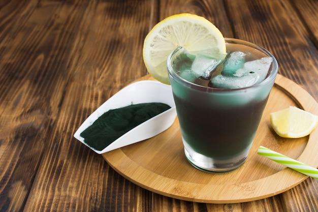 A boire avec de la chlorelle dans le verre sur le fond en bois marron. fermer.