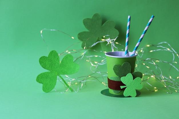 Boire dans des gobelets en papier en forme de chapeau de saint-patrick avec pailles, shamrock et illumination
