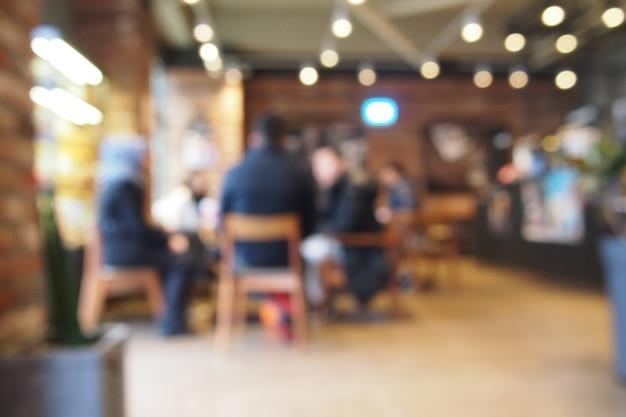 Boire du café avec des amis au café. fond de lentille floue.