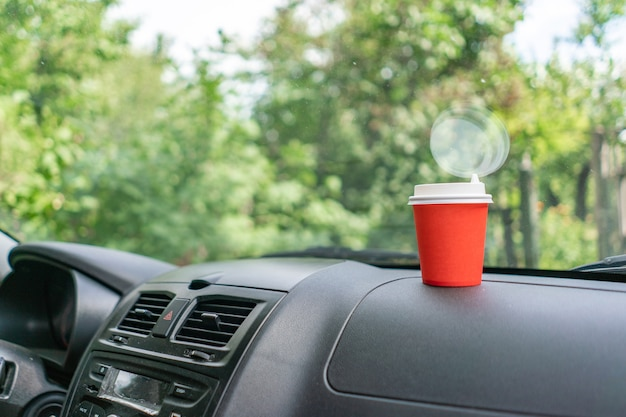 Boire du café dans une tasse en papier pendant le trajet en voiture