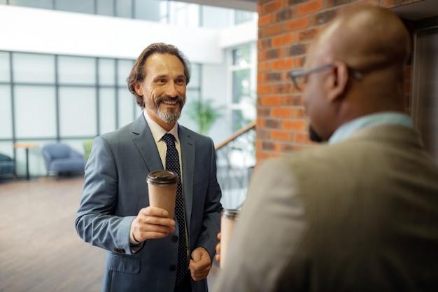 Boire du café à emporter. homme d'affaires aux cheveux gris buvant du café à emporter en attendant l'ascenseur avec un collègue