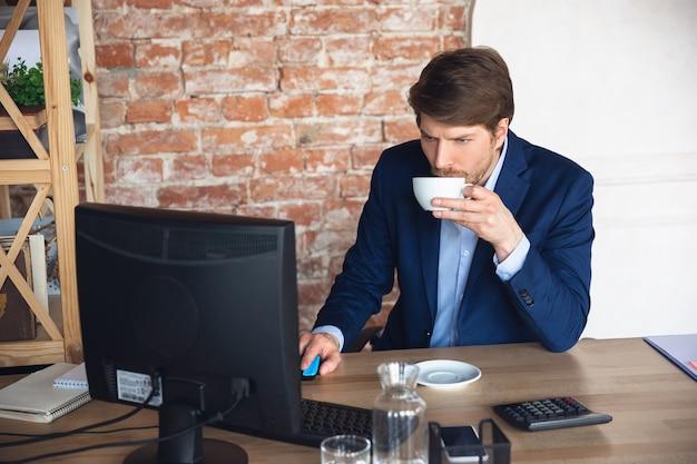 Boire du café inspiré, lire des tâches. jeune homme, directeur de retour au travail dans son bureau après la quarantaine, se sent heureux et inspiré. revenir à une vie normale. affaires, finance, concept d'émotions.