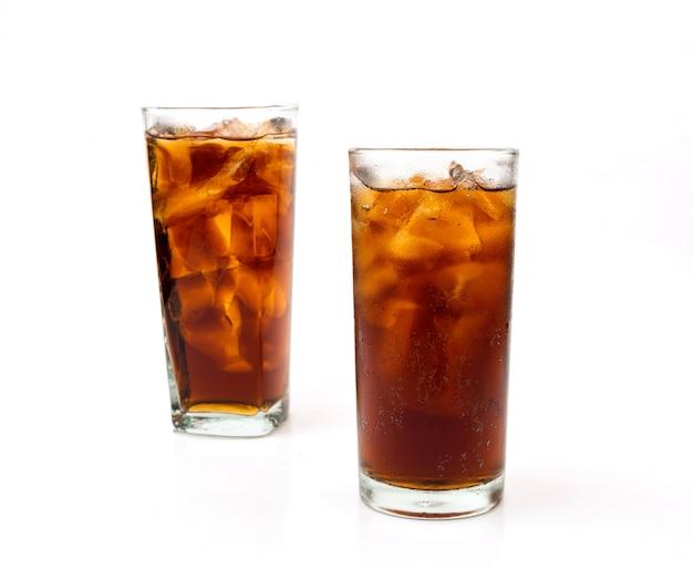 Boire du cola avec de la glace en verre sur fond blanc