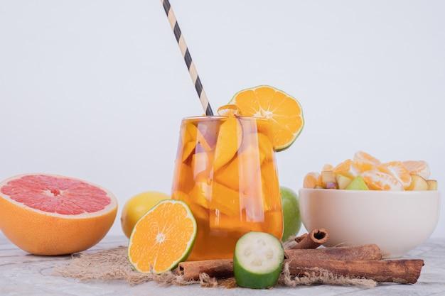 Boire avec du pamplemousse, du citron vert et de la cannelle sur blanc.