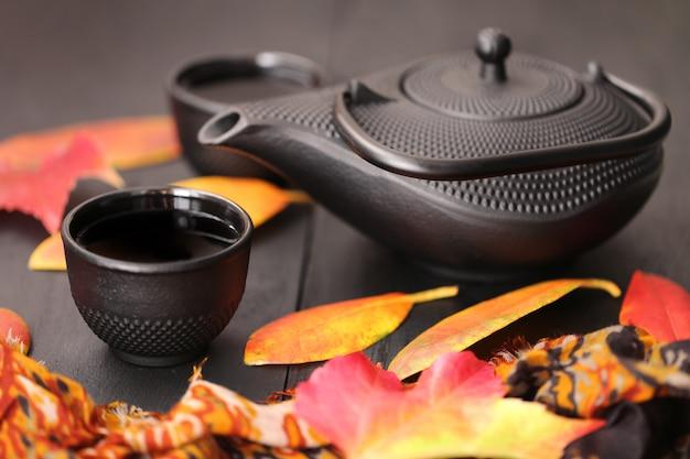 Boire du thé en automne. théière noire et feuilles d'automne