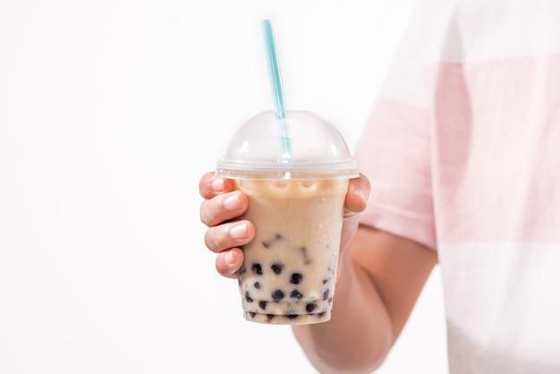 Boire du thé à bulles crémeux brun clair et des perles de tapioca noires dans des gobelets en plastique sur la table.