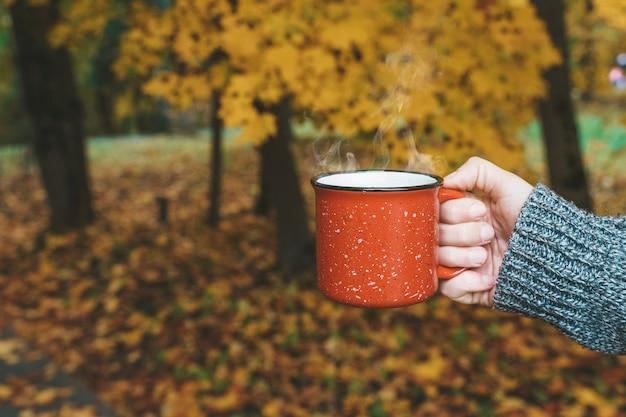 Boire du thé ou du café d'automne dans les mains sur fond de feuilles jaunes d'octobre confort d'automne