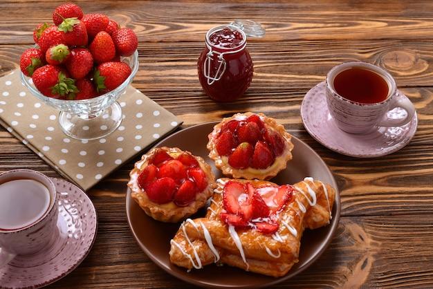 Boire du thé avec des tartelettes et des gâteaux aux fraises
