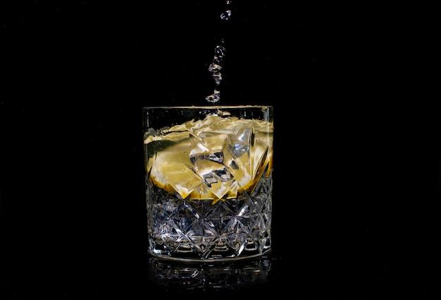 Boire de l'eau avec des déversements de soda au citron lorsque de la glace est jetée avec des gouttes