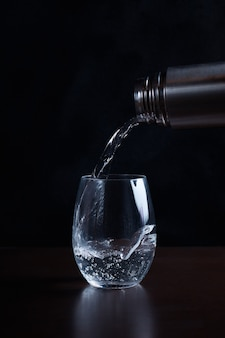 Boire de l'eau gazeuse est versé dans un flux d'une bouteille dans un verre transparent