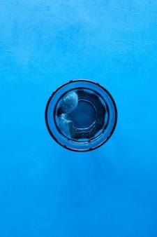 Boire de l'eau avec de la glace en verre bleu transparent