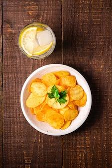 Boire de l'eau glacée fraîche avec du citron près de chips de pommes de terre frites ondulées dorées