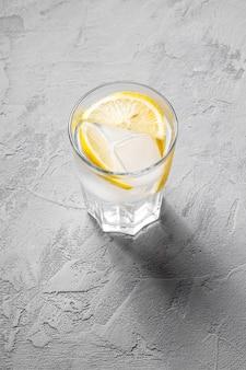 Boire de l'eau glacée fraîche avec du citron en verre sur mur de béton, vue d'angle