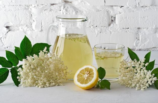 Boire des fleurs de sureau en carafe avec une tranche de citron contre un mur de briques blanches.