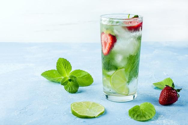 Boire avec de la fraise, du citron vert et de la menthe. limonades d'été ou thé glacé. cocktails mojito avec des glaçons.
