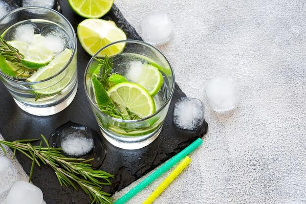 Boire avec de la glace, du citron vert et du romarin. vue de dessus avec espace de copie