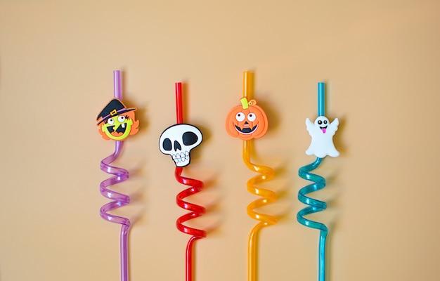 Boire des pailles avec un décor d'halloween. décorations amusantes pour les boissons pour bébés. fantôme, sorcière, citrouille et crâne sur des pailles.