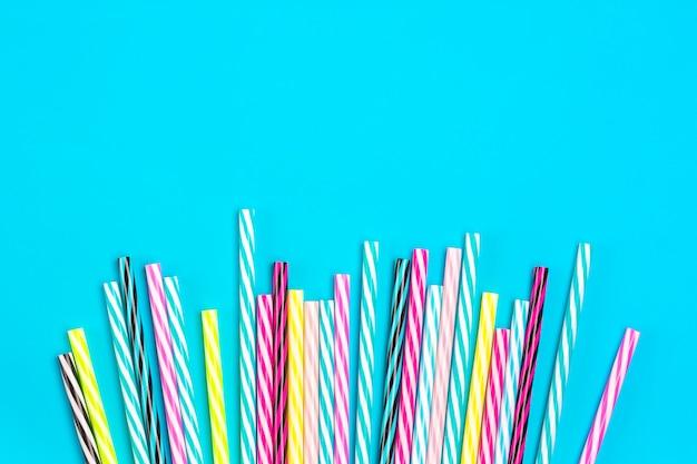 Boire des pailles avec des rayures pour la fête sur fond bleu