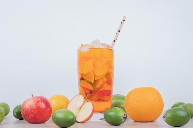 Boire avec pomme, feijoa et paille sur blanc