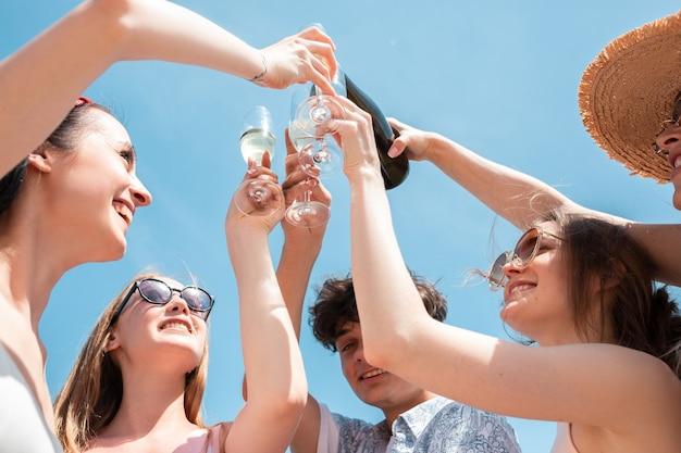 Boire, verser, acclamations. fête saisonnière à la station balnéaire. groupe d'amis célébrant, se reposant, s'amusant par une journée d'été ensoleillée. ayez l'air heureux et joyeux. temps festif, bien-être, vacances, fête.