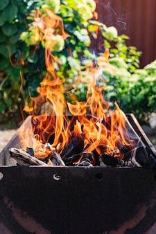 Bois de chauffage brûlant dans le gril. reposez-vous dans la nature. charbons ardents. feu de joie.