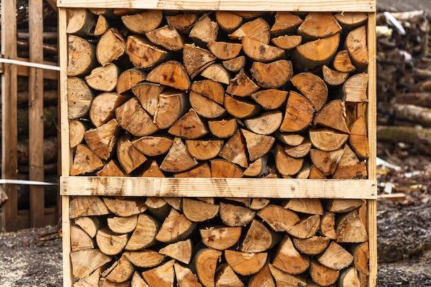 Bois de chauffage coupé, bois de chauffage coupé empilé dans des boîtes, fond de bois de feu.