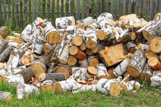 Bois de chauffage sur l'herbe verte. préparation des bois pour l'hiver. scène rurale.