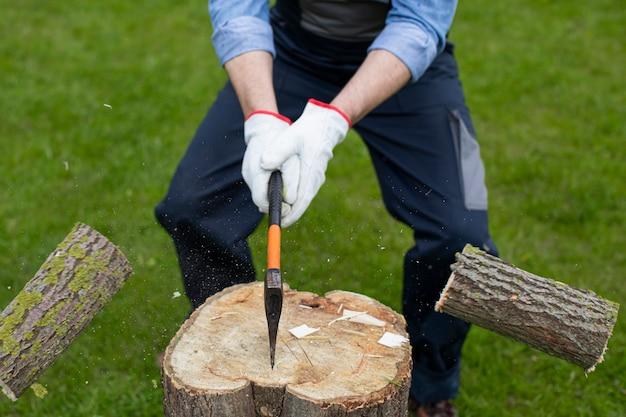 Le bois de chauffage se propage après avoir été frappé avec une hache sur une bosse